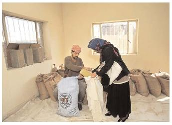 A woman gets her monthly distribution of food at a disaster-relief center in Baghdad. Following the 2003 war in Iraq, hundreds of relief agencies provided support to affected citizens. [Photograph by Caroline Penn. Corbis. Reproduced by permission.]