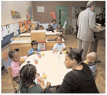Former U.S. Secretary of Agriculture Dan Glickman promotes federal food programs at a daycare center while the children behind him enjoy lunch. [Photograph by Mike Derer. AP/Wide World Photos. Reproduced by permission.]