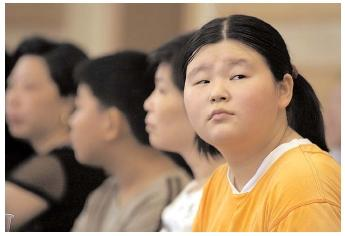 Young Chinese attend a weight-loss lecture in Shanghai. A trend toward obesity in many nations is accompanied by obsession over body image. During 2002, several citizens of Asian nations died and hundreds were sickened when they took a popular diet pill that was known to cause health problems. [AP/Wide World Photos. Reproduced by permission.]