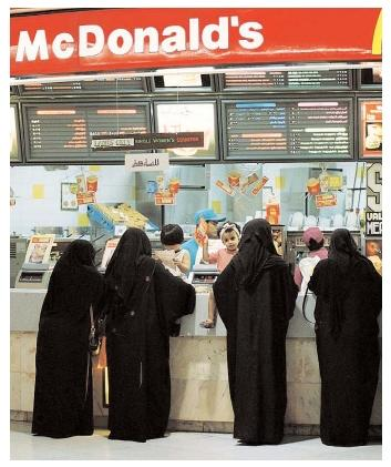 Abaya-wearing women in Saudi Arabia wait in the ladies-only line to order a quick meal. In developing nations, the popularity of fast-food alternatives to traditional cuisines has prompted debate over the nutritional and cultural impacts of Westernization. [Photograph by Saleh Rifai. AP/Wide World Photos. Reproduced by permission.]